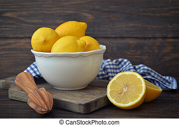 Lemons in a white bowl with lemon reamer on wooden...