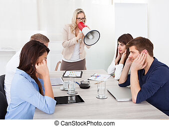Businesswoman Shouting Through Megaphone On Colleagues -...