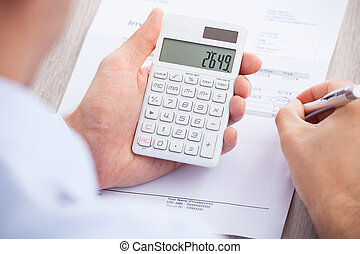Businessman Calculating Invoice At Desk - Cropped image of...