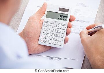 hombre de negocios, calculador, factura, en, escritorio