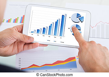 Businessman Comparing Graphs On Digital Tablet At Office...