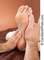 Therapist Giving Foot Massage To Female Customer At Spa -...