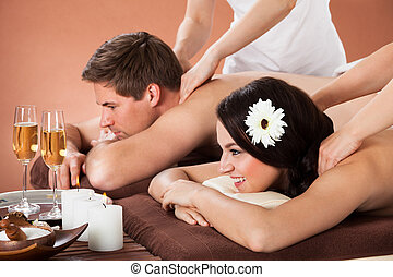 Relaxed Couple Enjoying Shoulder Massage At Spa - Relaxed...