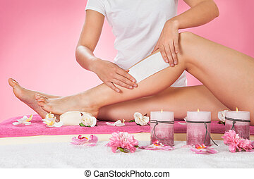 Therapist Waxing Customer's Leg At Spa - Midsection of...