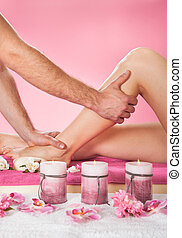 Therapist Massaging Customer's Leg At Beauty Spa