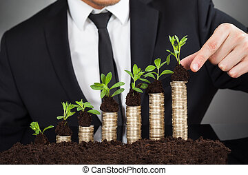 Businessman Stacking Saplings On Coins Representing Growth -...