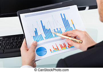 Businessman Analyzing Graphs At Office Desk