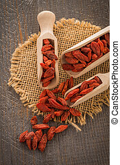 Goji berries on a wooden spoons, wooden background