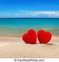 Two red hearts in the sand - Two red hearts in the sand on...