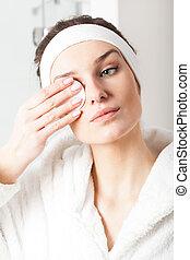 Beautiful woman removing make-up - Beautiful young woman...