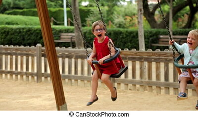 Two laughing children on swing in summer park