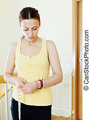 serious woman measuring waist with tape