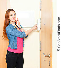 Red-haired girl using house videophone indoor - Red-haired...