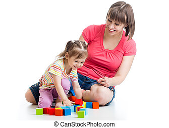 young woman and her dayghter kid play with building blocks
