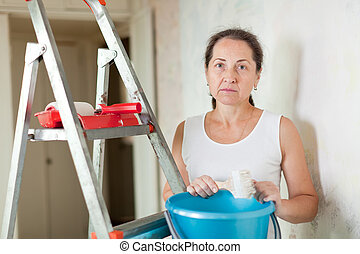 weariness woman makes repairs at home - weariness mature...