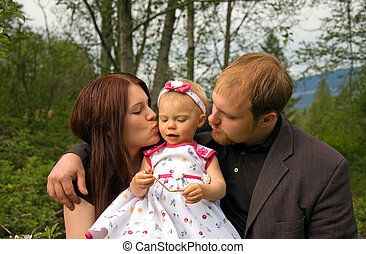 Young Family Kissing Baby
