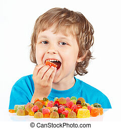 Little child eating candies on white background