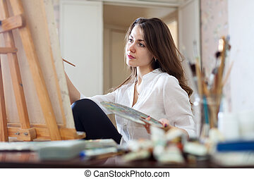 Long-haired woman paints picture on canvas - Long-haired...