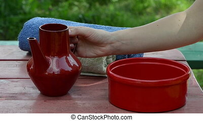 red clay bowl jug - hand woman pours water on a red clay...