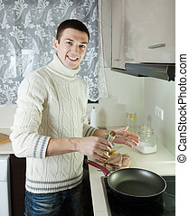 Handsome guy pouring oil in frying pan at home kitchen