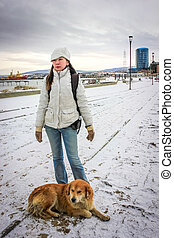 Woman stands with strayed dog