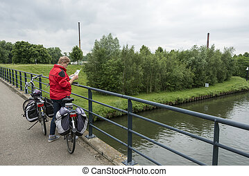 woman is looking at the map for the road - woman with bike...