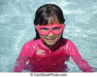 Girl in Pool - A little girl wearing goggles enjoys summer...