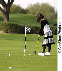 Girl Playing Golf - A young girl has fun playing golf on a...