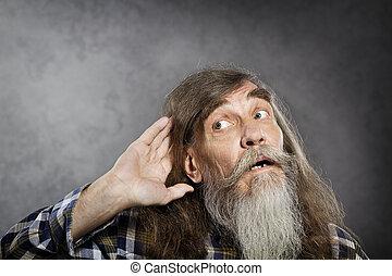 Senior man tries to listen sound. Elder hearing loss...