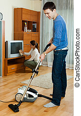 family cleaning with vacuum cleaner in living room -...