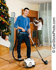 Adult couple doing housework - Adult couple cleaning with...