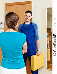 Housewife meeting repairing engineer at home - Housewife...
