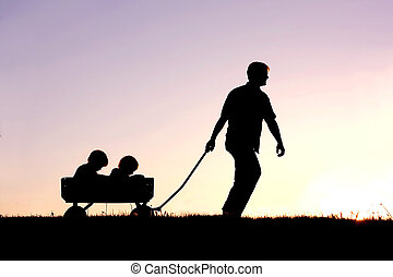 Silhouette of Father Pulling Sons in Wagon at Sunset - The...