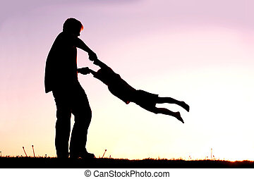 Silhouette of Father Playing with Child Outside at Sunset -...