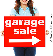 Garage Sale This Way - A young woman holding a signboard...