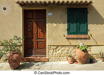 doorway to the tuscan house with ceramic vases and flowers, Ital