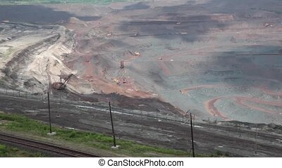 Heavy equipment digs and hauls ore inside huge open pit mine...