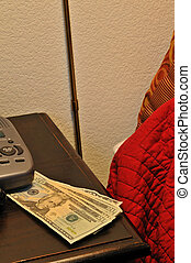 money on the bed - a stack of bills on a dresser next to the...