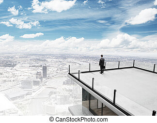 businessman on roof - businessman standing on roof of...