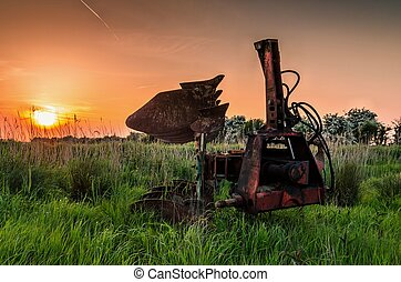 Plough standing in grass at sunset