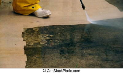 Pressure cleaning - worker cleaning a dirty old driveway