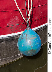 Fender of an old fishing boat - Blue fender of an old...