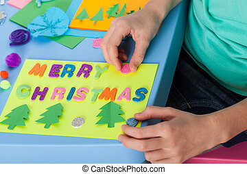 The child makes a Christmas card in kindergarten