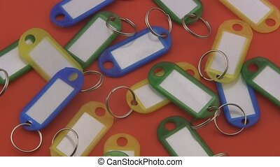 Key tags on a red background - Assorted coloured key tags...