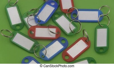 Key tags on a green background. - Assorted coloured key tags...