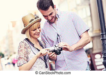 Young couple checking pictures on their camera - A picture...