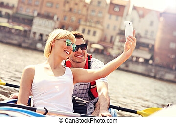 Young couple taking pictures in a canoe - A picture of a...