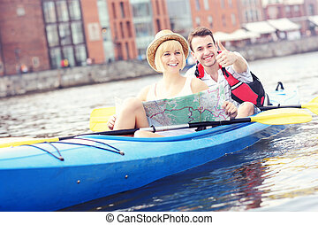 Happy tourists with a map in a canoe
