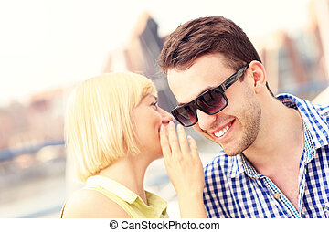 Woman whispering to boyfriend - A picture of a woman...