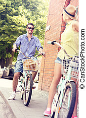 Young man cycling with his girlfriend